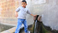 Exterior shots of young boy dressed in jeans and a jumper drinking from water coming out of hole in the wall in Battir near Bethlehem Israel on in...