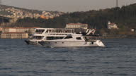 Exterior shots of young people hanging out and taking selfies on the shore of the Bosphorus and tour boats passing near the Bosphorus Bridge on April...
