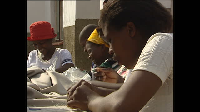 Exterior shots of Zulu village women sewing beads onto fabric by hand working together on July 7 2002 in KwaZuluNatal South Africa