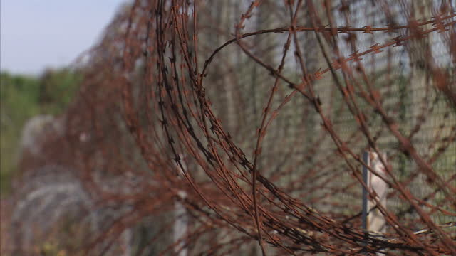 Exterior shots old rusted barbed wire fencing running along rail tracks close to Calais port with warning signage on fencing on August 02 2016 in...