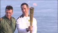 exterior shots Olympic Sailing Gold Medallist Ben Ainslie standing with burning Olympic Torch at Land's End Ben Ainslie Starts Olympic Torch Relay at...