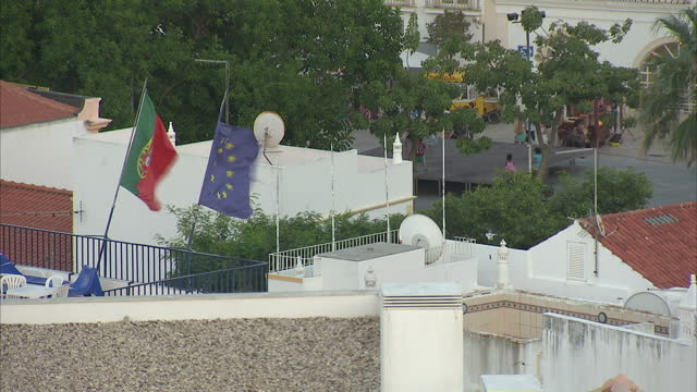 Exterior shots over villa and hotel rooftops of the holiday resort of Albufeira including tourists walking in backstreets and the sea and bay area at...