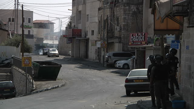 Exterior shots Palestinian men standing behind cars throwing objects at Israeli border police standing at end of road on October 05 2015 in Jerusalem...