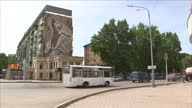Exterior shots people and vehicles in Karaganda town square with large mural of Yuri Gagarin Russian Soviet astronaut on side of building on June 16...