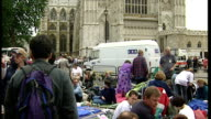 Exterior shots people camping waiting outside Westminster Abbey reading newspapers OK magazine on in London England