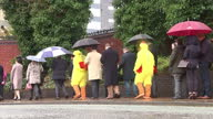 Exterior shots people dressed as chickens holding signs saying 'Cameron Is The Real Debate Chicken' queue up with delegates waiting to enter the...