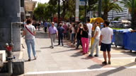 Exterior shots people queue along street waiting to withdraw cash from ATM machine after Greek Government imposed capital controls on June 26 2015 in...