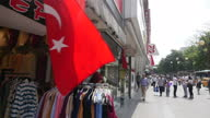 Exterior shots people walking along busy street in the centre of Ankara past various shops with Turkish flags flying on July 26 2016 in Ankara Turkey