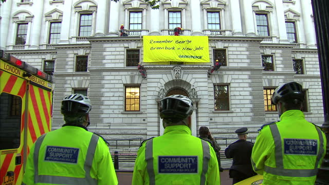 Exterior shots police look on as Greenpeace activists hang banner on the HM Treasury building Exterior shots Greenpeace activists hanging from...