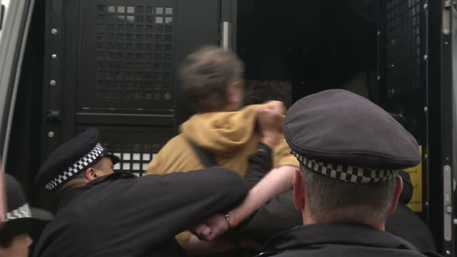 Exterior shots police officers arresting antiausterity protester outside the Houses of Parliament and put protester into back of police van on budget...