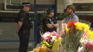 Exterior shots police officers walking around at the scene where Polish man Arkadiusz Jozwik was stabbed and shots of floral tributes in street on...