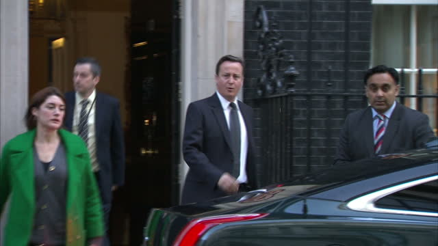 Exterior shots Prime Minister David Cameron walks out from Number 10 Downing Street with aides gets into waiting car which drives off in convoy David...
