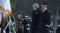 Exterior shots Prime Minister Theresa May walks up steps with US military officer at Arlington Cemetary lays wreath at the Tomb of the Unknowns...