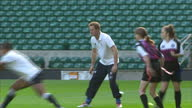 Exterior shots Prince Harry in girls training session passing rugby ball running around Prince Harry In Girls Rugby Training Session at Twickenham...