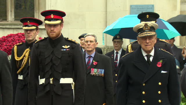 Exterior shots Prince Philip Duke of Edinburgh and Prince Harry both wearing ceremonial uniforms stand as the Dean of Westminster John Hall speaks...
