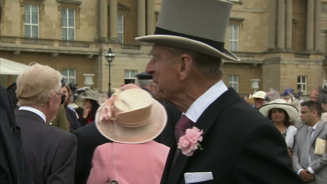 Exterior shots Prince Philip Duke of Edinburgh talking with guests at Buckingham Palace garden party on May 22 2014 in London England