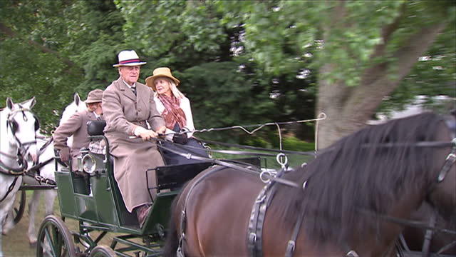Exterior shots Prince Philip sat holding reigns of carriage Exterior shots Prince Philip moves off on carriage Exterior shots Prince Philip drives...