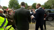 Exterior shots Prince William accepts gift from crowd behind barrier gets in to waiting car and departs