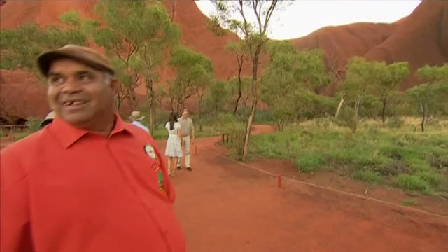 ULURU exterior shots Prince William and Catherine Duchess of Cambridge reading information board pan out to Ayers rock in front of them Prince...