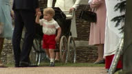 Exterior shots Prince William crouched down talking to Prince George of Cambridge outside Church of St Mary Magdalene Prince George walks off on July...