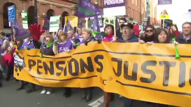 Exterior shots public sector workers marching in strike protest carrying large banners placards through Manchester street Public Sector Strike...