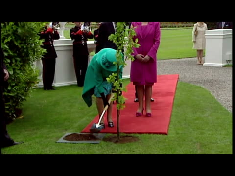 Exterior shots Queen Elizabeth helps to plant Irish oak tree at Aras an Uachtarain with Mary McAleese alongside Exterior shots the peace bell being...
