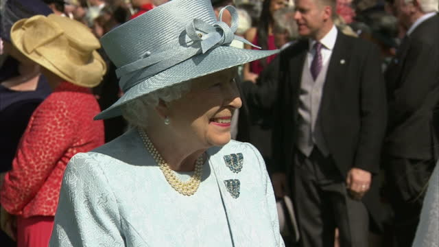 Exterior shots Queen Elizabeth II talking with guests at Red Cross garden party at Buckingham Palace on June 10 2014 in London England
