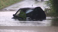 Exterior shots rescue worker comes to the aid of a person trapped in their half submerged car which is stuck in deep flood waters Car Being Rescued...