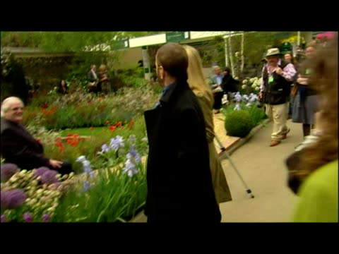 Exterior shots Ringo Starr wife Barbara Bach walk through the Chelsea Flower show over to the George Harrison Memorial Garden