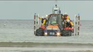 Exterior shots RNLI amphibious tractor towing a lifeboat and crew from the sea across low tide and onto beach in Redcar on 1st of August 2017
