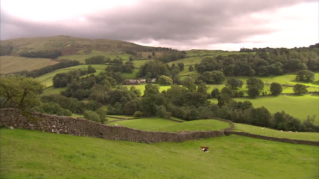 Exterior shots rolling hills countryside with dry stone walls fields with cottages stone buildings in valley Cumbrian Countryside Shots on August 29...