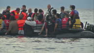 Exterior shots rubber dinghy crowded with refugees paddling towards shore some people in water swimming and helping to guide boat Exterior shots...