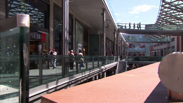 Exterior shots shoppers walking around Liverpool One shopping complex on wet but sunny day on July 08 2015 in Liverpool England