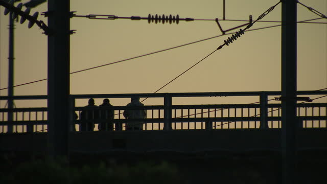 Exterior shots silhouettes of migrants hanging around on bridge as vehicles pass near to Calais port on August 02 2016 in Calais France