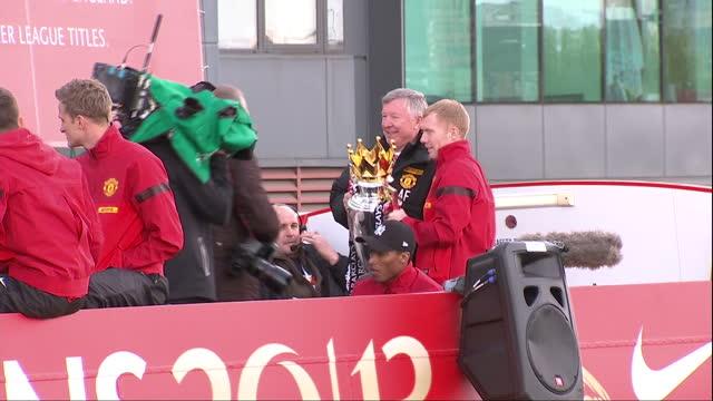 Exterior shots Sir Alex Ferguson Manchester United manager posing with Premier League trophy players Paul Scholes Antonio Valencia on an open top bus...