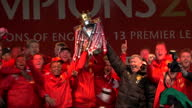 Exterior shots Sir Alex Ferguson Manchester United players lift Premier League trophy dance around on stage whilst singing along to Queen 'We are the...