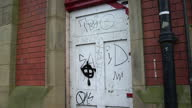 Exterior shots smashed window pane Exterior shots graffiti on walls doors in run down area Graffiti on Buildings in Leeds on December 13 2012 in...