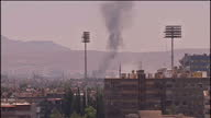Exterior shots smoke plume rising over buildings in Damascus Exterior wide shots smoke plume rises over buildings in suburb Bomb Explosions in...