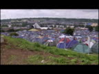 Exterior shots tents at campsite Wide high shots Glastonbury festival site General shots festival goers washing themselves sitting around campsite...