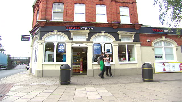 Exterior shots Tesco Express supermarket in Twickenham London Includes shots of signage and shoppers leaving shop Tesco has reported a 235% drop in...