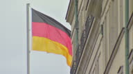 Exterior shots The Brandenburg Gate tourists in streets German flag blowing in wind Wurst food street seller on May 28 2015 in Berlin Germany