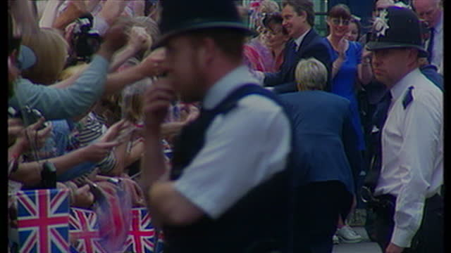 Exterior shots Tony Blair waving to crowds Cherie Blair Tony Blair shaking hands with crowds of people waving British flags on May 2nd 1997 in London...