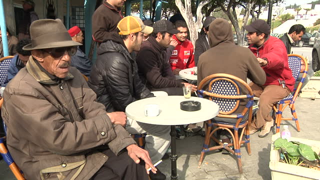 Exterior shots Tunisian men sitting in outdoor cafe area drinking coffee smoking talking on January 25 2011 in Tunis Tunisia