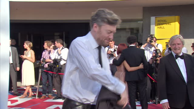 exterior shots TV presenter writer columnist Charlie Brooker joking and posing for photographers on red carpet at Arqiva British Academy Film Awards...