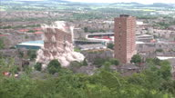 Exterior shots two high rise flats demolished with controlled explosion with dust thrown into air and Dundee football grounds in the background Two...