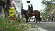 Exterior shots two NYPD mounted police officers on horses stationary outside a convenience store on 12th August 2010 in New York United States