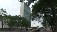 Exterior shots United Nations UN building headquarters in New York with UN signage flags outside Exterior shot street signs for United Nations Plaza...