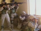 exterior shots US Marines street fighting in city firing from room in tower block bullets hitting buildings Marines cross streets Assault Amphibious...
