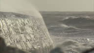 Exterior shots waves crashing over sea defences with strong wind blowing spray over wall on in Somerset United Kingdom