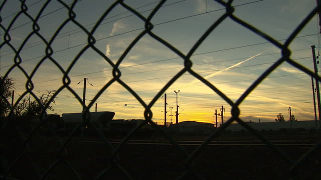 Exterior shots wire fencing running alongside rail tracks at Calais Port at dusk on August 02 2016 in Calais France